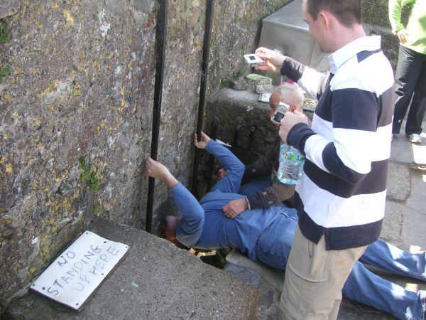 Un turista besando la piedra de la elocuencia del castillo de Blarney