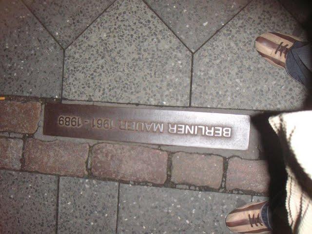 Con un pie en cada parte del muro de Berlín