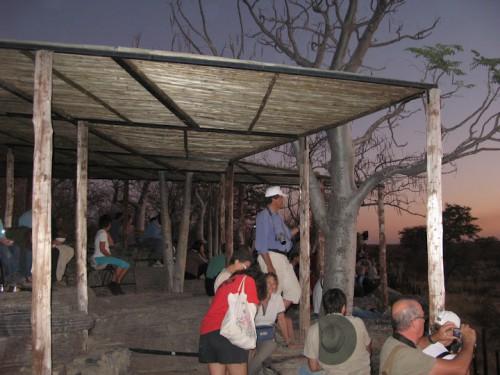 Gente en las gradas de la charca de Halali en Etosha Park durante la puesta de sol