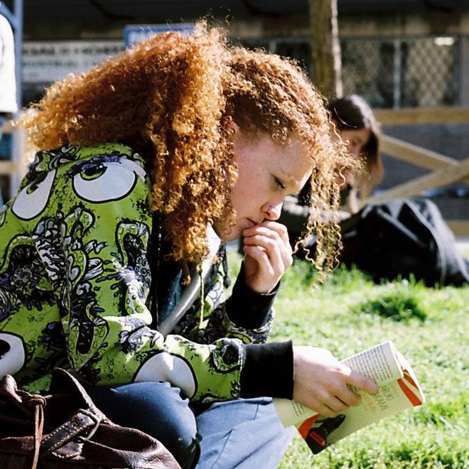 Chica concentrada leyendo un libro en la plaza de Tallers, Barcelona